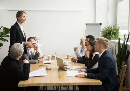 successful-female-boss-leading-team-meeting-talking-to-multiracial-employees